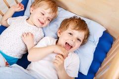 Deux petits garçons d'enfant en bas âge ayant l'amusement et le combat Photographie stock