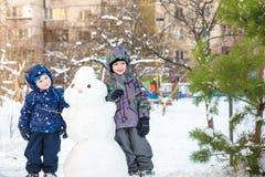 Deux petits garçons d'enfants d'enfants de mêmes parents faisant un bonhomme de neige, jouant et ayant l'amusement avec la neige, Images stock