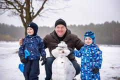 Deux petits garçons d'enfants de mêmes parents faisant un bonhomme de neige avec le grand-père, jouant et ayant la neige d'amusem Photos stock