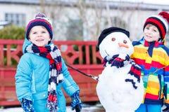 Deux petits garçons d'enfants de mêmes parents faisant un bonhomme de neige, jouant et ayant le fu Images libres de droits
