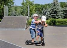 Deux petits garçons discutant au sujet d'un scooter Image libre de droits