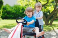 Deux petits garçons drôles ayant l'amusement avec la voiture de course dehors Photos libres de droits