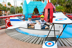 Deux petits garçons drôles d'enfant montant sur le carrousel de rond point Images stock