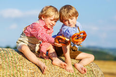 Deux petits garçons et amis d'enfant de mêmes parents s'asseyant sur la pile de foin et l'ea Photographie stock libre de droits