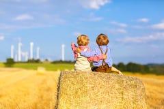 Deux petits garçons et amis jumeaux s'asseyant sur la pile de foin Photos libres de droits