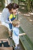 Deux petits garçons et animaux alimentants de mère dans le zoo Photographie stock libre de droits