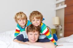 Deux petits garçons et papa d'enfant d'enfant de mêmes parents ayant l'amusement dans le lit après slee Photographie stock