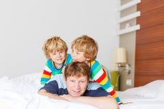 Deux petits garçons et papa d'enfant d'enfant de mêmes parents ayant l'amusement dans le lit après slee Photos stock