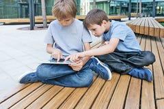 Deux petits garçons jouant avec le PC de comprimé, dehors Images stock