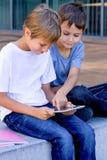 Deux petits garçons jouant avec le PC de comprimé, dehors Photos stock