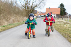 Deux petits garçons jumeaux d'enfant en bas âge ayant l'amusement sur des bicyclettes, dehors Photographie stock