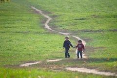 Deux petits garçons marchant ensemble sur le chemin Image stock