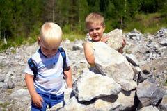 Deux petits garçons mignons construisant ensemble la tour des pierres Photographie stock libre de droits