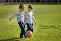 Deux petits garçons mignons, jouant le football Photo stock