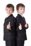 Deux petits garçons mignons jumelle dans des pouces de costumes  Image stock