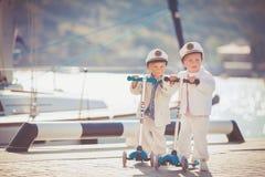 Deux petits garçons montant sur le scooter vont à vélo en été Photo libre de droits