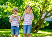 Deux petits garçons préscolaires d'enfant mangeant la pastèque en été Photos libres de droits