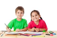 Deux petits gosses dessinent avec des crayons Images stock