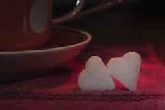 Deux petits morceaux de sucre sous forme de coeurs Image stock