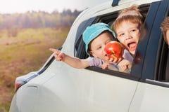 Deux petits passagers ayant l'amusement voyageant en voiture photo stock
