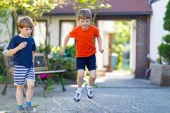 Deux peu de garçons d'enfants d'école et d'école maternelle jouant le jeu de marelle sur le terrain de jeu Photographie stock libre de droits