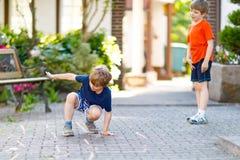 Deux peu de garçons d'enfants d'école et d'école maternelle jouant le jeu de marelle sur le terrain de jeu Photographie stock