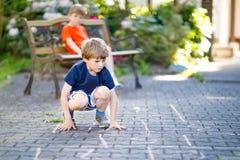 Deux peu de garçons d'enfants d'école et d'école maternelle jouant le jeu de marelle sur le terrain de jeu Photos stock