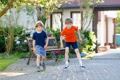 Deux peu de garçons d'enfants d'école et d'école maternelle jouant le jeu de marelle sur le terrain de jeu Photo stock