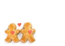 Deux peu tombés dans le chiffre de pain d'épice d'amour et entre deux peu de chiffre sont un amoureux rouge. Image stock