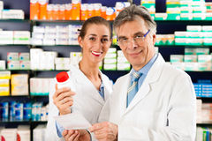 Deux pharmaciens dans la consultation de pharmacie image stock