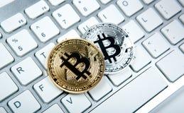 Deux pièces de monnaie de bitcoin sur le clavier blanc d'ordinateur portable Images stock