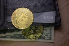 Deux pièces de monnaie de bitcoin sur un portefeuille avec des dollars image stock