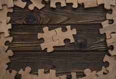 Deux pièces du puzzle sont reliées au centre sur une texture en bois dans un cadre des morceaux d'un puzzle Photo stock