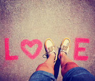 Deux pieds faisant un signe pour la lettre V dans l'amour de mot ont modifié la tonalité avec un rétro effet de filtre d'instagra Images libres de droits