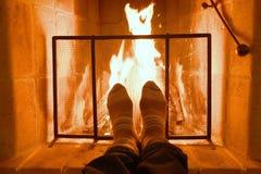 Deux pieds réchauffant devant la cheminée Image stock