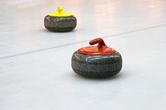 Deux pierres de granit pour le jeu s'enroulant sur la glace Photographie stock