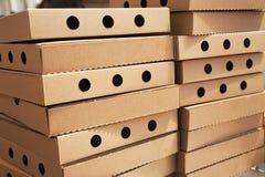 Deux piles de nouvelles boîtes fermées à pizza avec des trous photos libres de droits