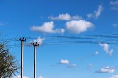 Deux piliers concrets et poteau en bois électrique contre le ciel bleu et les nuages photos libres de droits