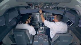 Deux pilotes s'asseyent dans une carlingue d'avion et discutent quelque chose clips vidéos