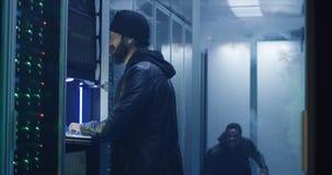 Deux pirates informatiques finissant l'entaille et échappant à une salle enfumée photos libres de droits