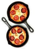 Deux pizzas de pepperoni simples de poêle de service au-dessus de blanc Photo libre de droits