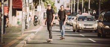 Deux planchistes montant la planche à roulettes inclinent sur les rues de ville Image stock