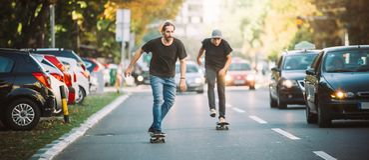 Deux planchistes montant la planche à roulettes inclinent sur les rues de ville Photo stock