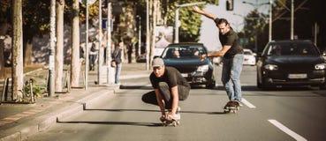Deux planchistes montant la planche à roulettes inclinent sur les rues de ville Photographie stock