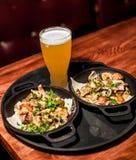 Deux platoes chauds savoureux de viande avec de la bière images stock
