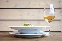 Deux plats avec des salades une et un verre de vin blanc fin photographie stock libre de droits