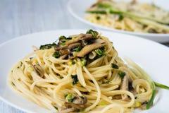Deux plats de pâtes avec des champignons et des oignons verts d'un plat blanc Images stock