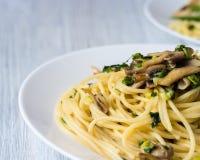 Deux plats de pâtes avec des champignons et des oignons verts d'un plat blanc Photo stock