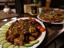 Deux plats orientaux avec du boeuf, le poulet, les tomates, les carottes, le poivron rouge et les nouilles de riz image stock