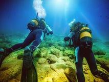 Deux plongeurs nageant à partir de l'appareil-photo Photographie stock libre de droits